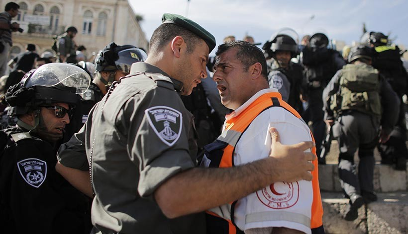 "A Palestinian medic argues with an Israeli border policeman during a demonstration marking the 66th anniversary of the ""Nakba,"" meaning catastrophe, when many Palestinians fled or were expelled from their towns and villages during the war of Israel's foundation in 1948, at Damascus Gate in Jerusalem's Old City May 15, 2014. An Israeli police spokesman said on Thursday that 5 Palestinian protesters were detained during the unauthorized demonstration in Jerusalem's Old City, where stones were thrown at policemen and an Israeli flag was burnt. Also on Thursday, Israeli forces shot dead two Palestinians during a stone-throwing protest marking the ""Nakba"" in the occupied West Bank. REUTERS/Ammar Awad (JERUSALEM - Tags: POLITICS CIVIL UNREST TPX IMAGES OF THE DAY) - RTR3PBX4"